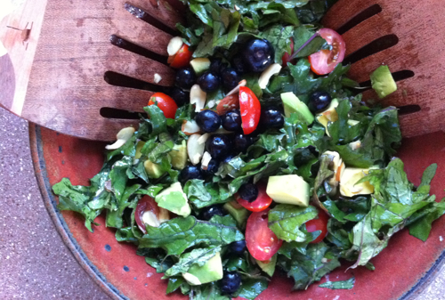 Raw kale salad with lemon, blueberries, grape tomatoes, avocados, and slivered almonds.